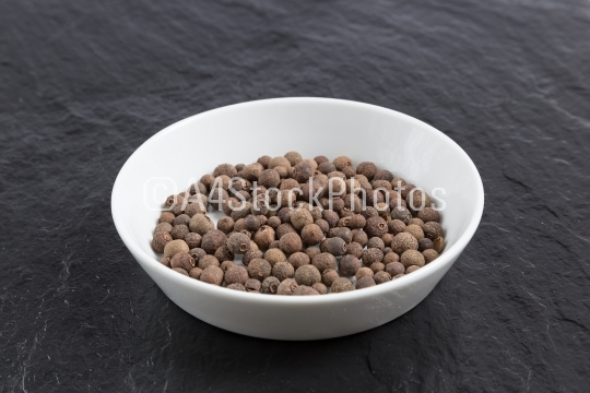 Allspice in a bowl on a slate