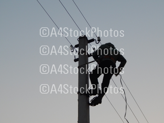 Electrician works in special clothes on the pole