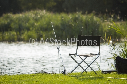 Fishing tackle on the bank, with sunlit water