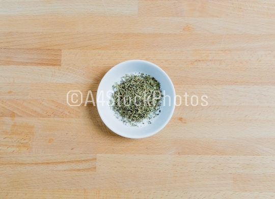 Provencal herbs in a bowl on wood
